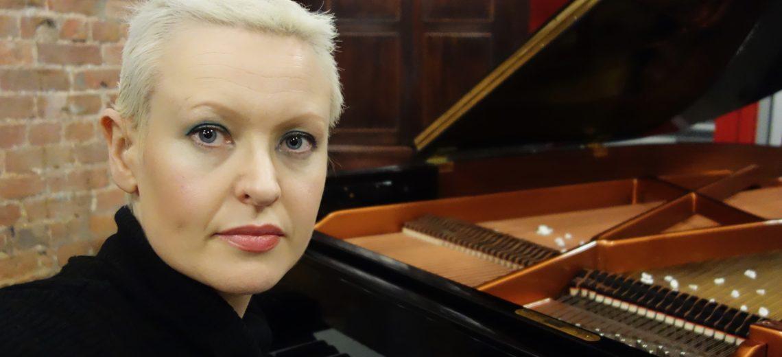 Woman with short hair sitting at piano