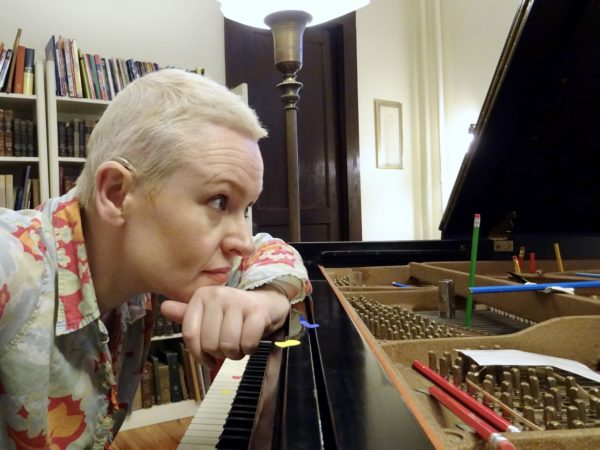White female with short blonde hair looking into piano
