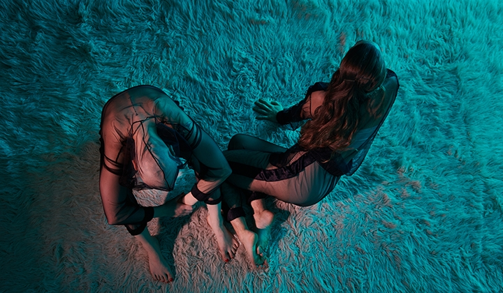 Two bodies from above bathed in bluish-bronze light, on a soft flokati carpet. They are wearing transparent tracksuits, their skin color is white, they are barefoot. The person on the left rests their arms on their drawn knees, holds their left wrist with their right hand. The head falls between the legs. The person next to them lies on their right side. With the bent legs crossed and leaning on their hands, they look forward to the right - beyond the picture. They touch the other with the tips of their feet. One remains, the other seems to leave the place in the next moment. Long dark hair, no hair, black mesh on skin.