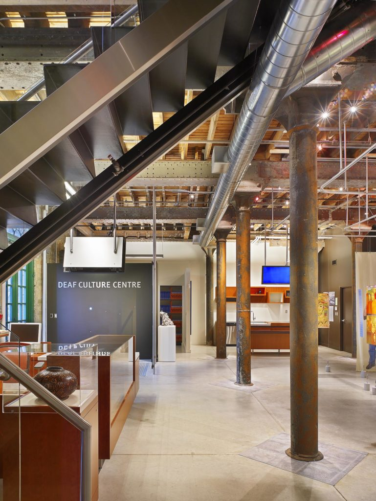 A sleek high-ceilinged and redesigned warehouse space with exposed ceilings, pillars and silver heating ducts. Various artworks hanging or in glass cases, a library, a reception desk, a small kitchen space, various projection screens and hanging televisions throughout. A large sign says DEAF CULTURE CENTRE.