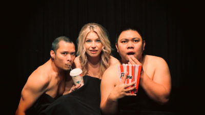 Three artists stare into the camera as if watching a film. They're naked but covered by a black cinema curtain. On the left is a man from Fairford Reserve with short black hair and a moustache. He drinks from a straw from the cinema-style drink held by a blonde white woman of Polish background to his right. On her right, a Filipino-Canadian with short black hair holds a cardboard popcorn box in one hand, while his other hand is at his mouth in surprise or fear.