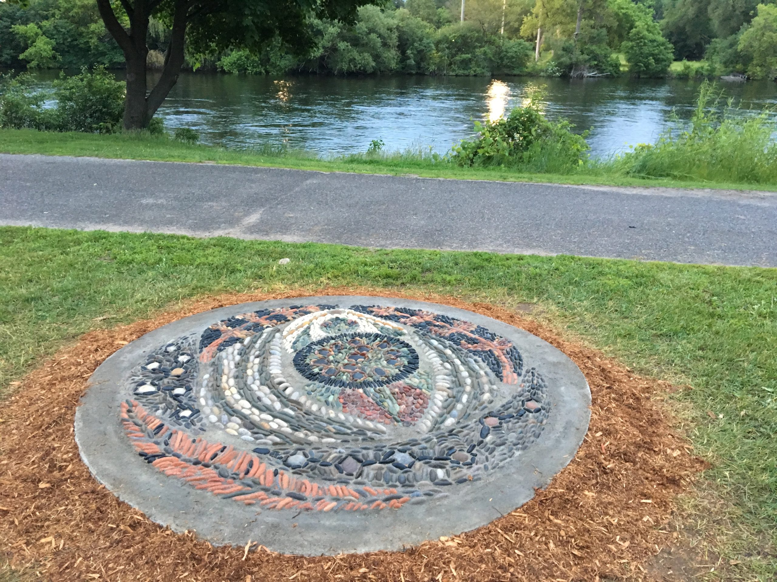 A two metre in diameter stone mosaic is in the foreground. The mosaic features the image of a turtle (Turtle Island), surrounded by cedar trees and water. It's made of red, black, white, tan and grey stones, and surrounded by cedar mulch and grass. In the background, an asphalt path, the Otonobee river, green grass and trees.