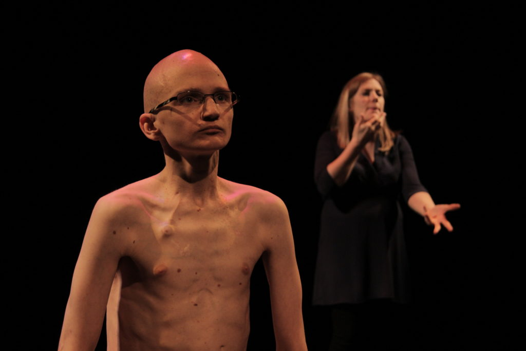 A baldheaded young white man directs a penetrating gaze at the audience. He is shirtless and his translucent skin stretches over his clearly defined rib cage and collarbones. A permanent IV port just under his skin is visible on the upper right side of his chest. Behind him is an out-of-focus ASL interpreter.