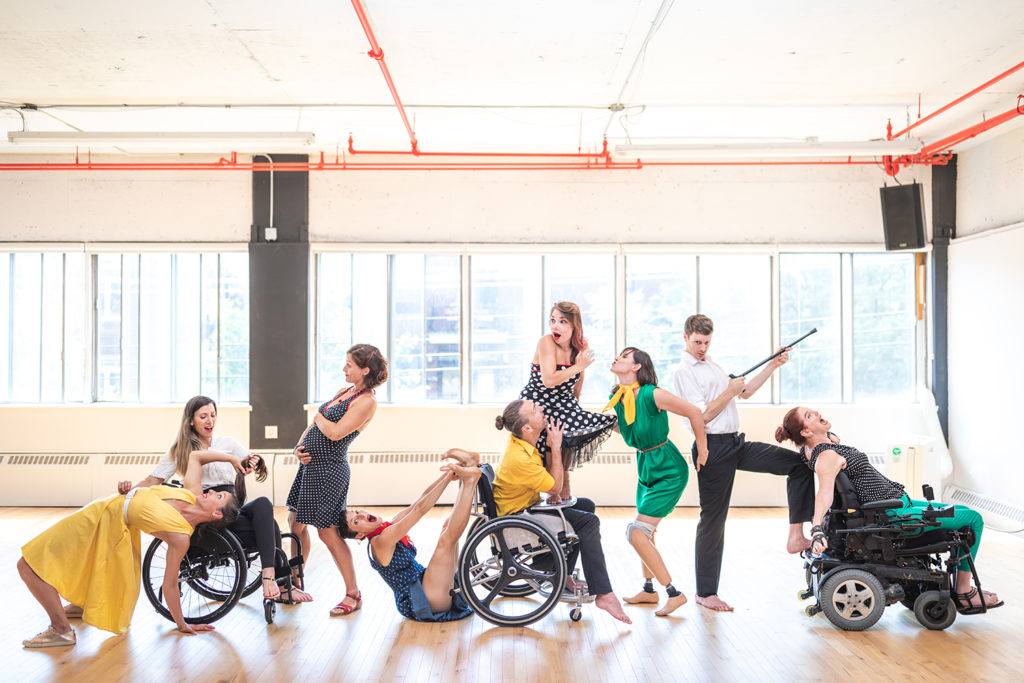 Dance troupe in a dance studio lined up. The dancers are white with a range of imapairments including wheelchair users and amputees. Their is also a pregnant woman holding her bump.
