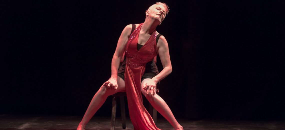 Two dancers centre stage. One is perched on a wooden chair, her body angled to the right. Her head is tilted back. One hard is pressing on her chest and the other on her hip. Her arms are energised and angular. Her legs are stretched out wide. The second dancer stands behind her. Her body posed to the right, and her head turned, focused on the dancer on the chair. They are both dressed in a vibrant red colour and the stage is black.