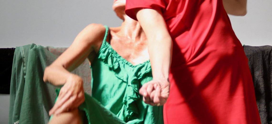 There are two dancers. One is standing in front, wearing a short red dress and she is staring down towards the camera lens. One arm is by her face, and the other by her side. The other dancers is perched on a chair behind, dressed in a light green dress. We see half her face. She is crossing her legs, and in a poised, reclining position. The photo is taken in a bright studio.
