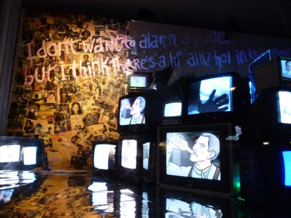 Installation view of an exhibition. On the left of the image is a tree-shaped collage of many, many black and white images (it's not very clear as the images are small, but some are portraits of people) - they are lit in a sunshine yellow light. The floor of what is assumed to be a gallery is chrome, and reflects the rest of the room. 12 TV monitors make a wall on the right of the image, on 2 screens are an animation of a man drinking from a bottle, on another is a hand touching the screen, other screens are whited out or unclear.