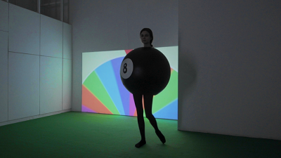 A performer in black dressed dressed as a billiard ball, in front of a colourful spinning wheel