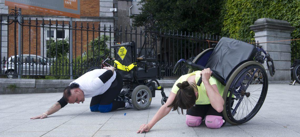 Two wheelchair dancers kneel in a street performance