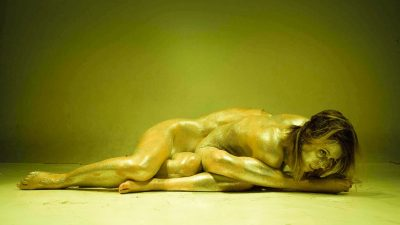 A gold-tinted photo of a female nude performer lying on the ground, covered in glitter