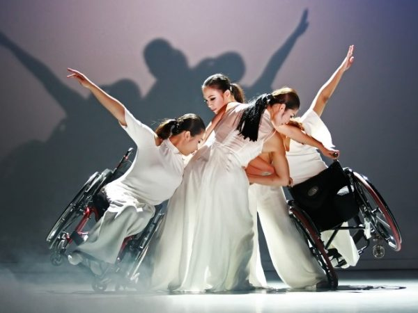 East Asian dancers in white clothing huddle together with two wheelchair users on the edge of the huddle leaning in