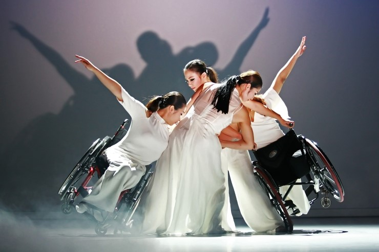 Four female South Korean performers all in white, two rock in their wheelchairs at the sides forming a unified shape with arms outstretched.