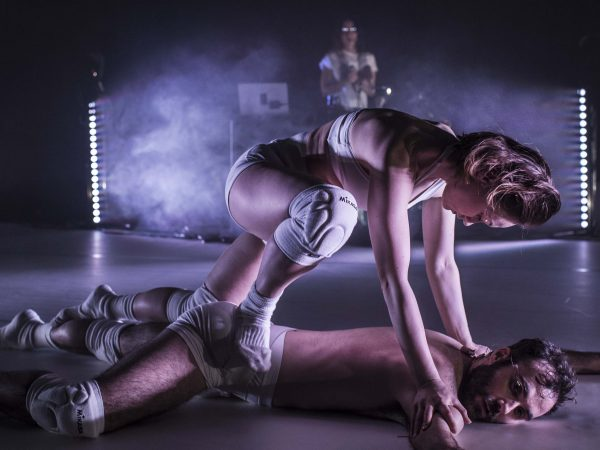 A dancer is climbing on another dancer who is lying on the floor