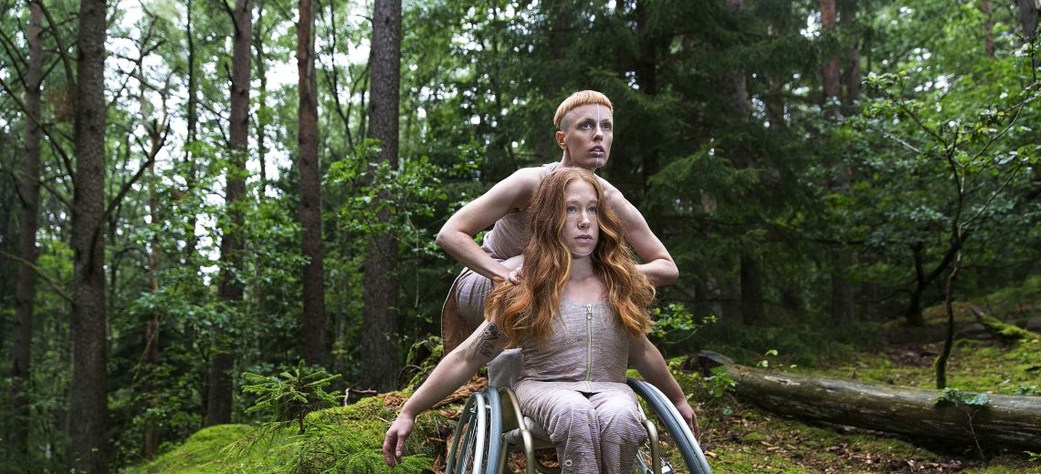 Two dancers are in forest. One dancer is in a wheelchair and the other dancer is squatting behind.
