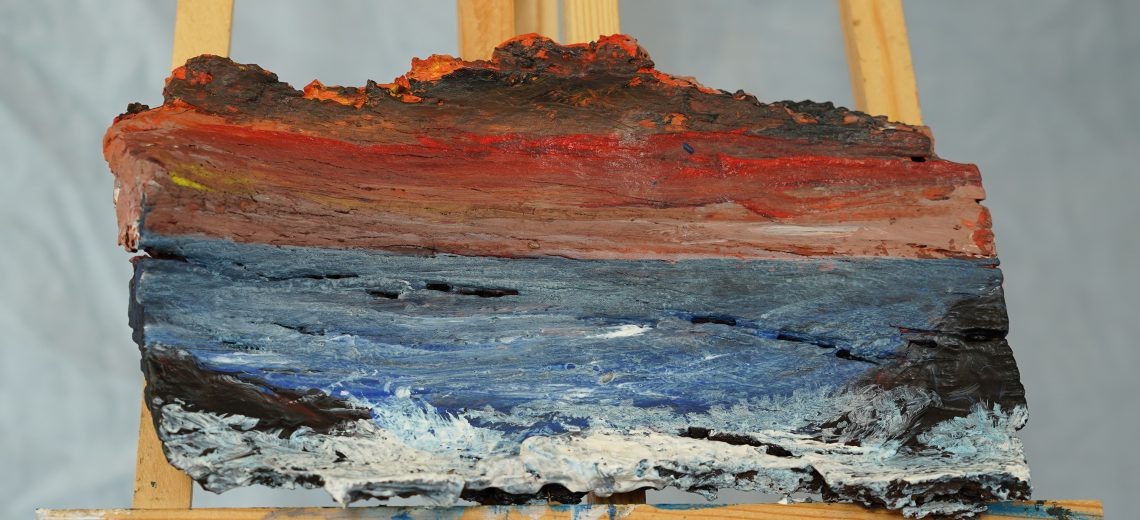 Photograph of a painting of a seaside scene done on a piece of driftwood