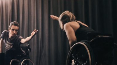 A male and female duo using wheelchairs reach their hands across to join each other