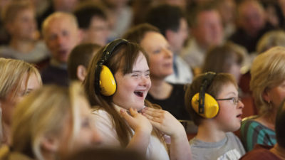 Photograph of a theatre crowd, some of whom are learning disabled and wearing ear defenders