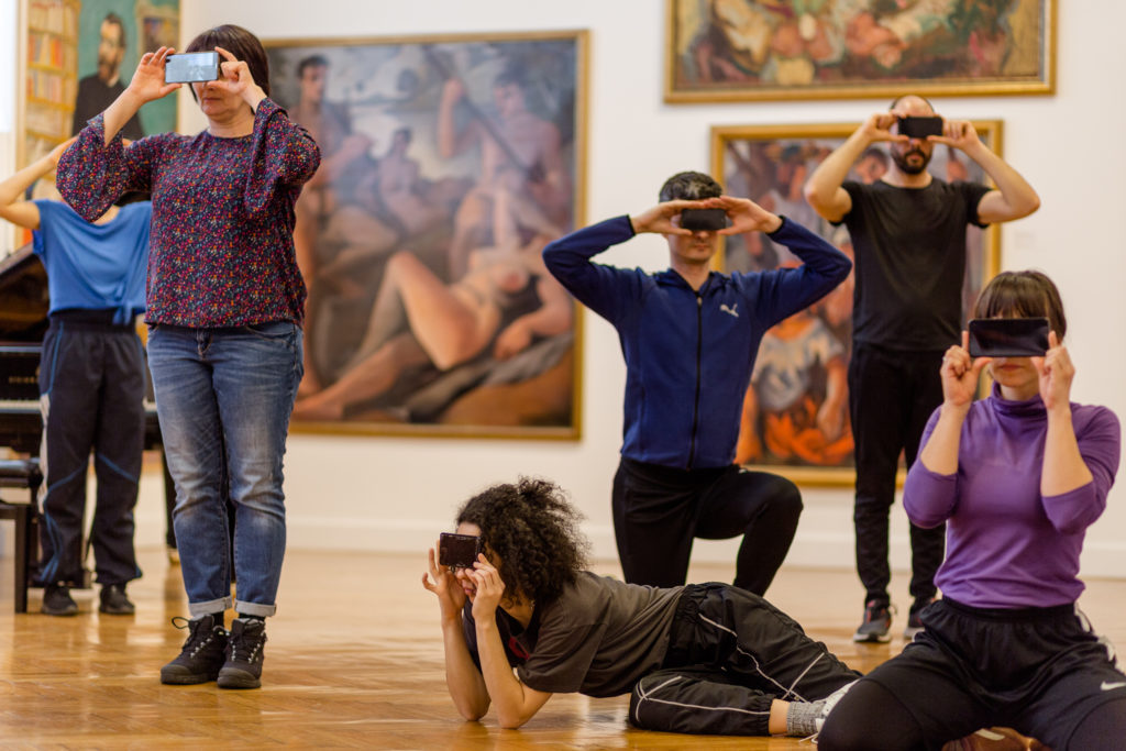 A group of performers pose with their camera phones covering their eyes.