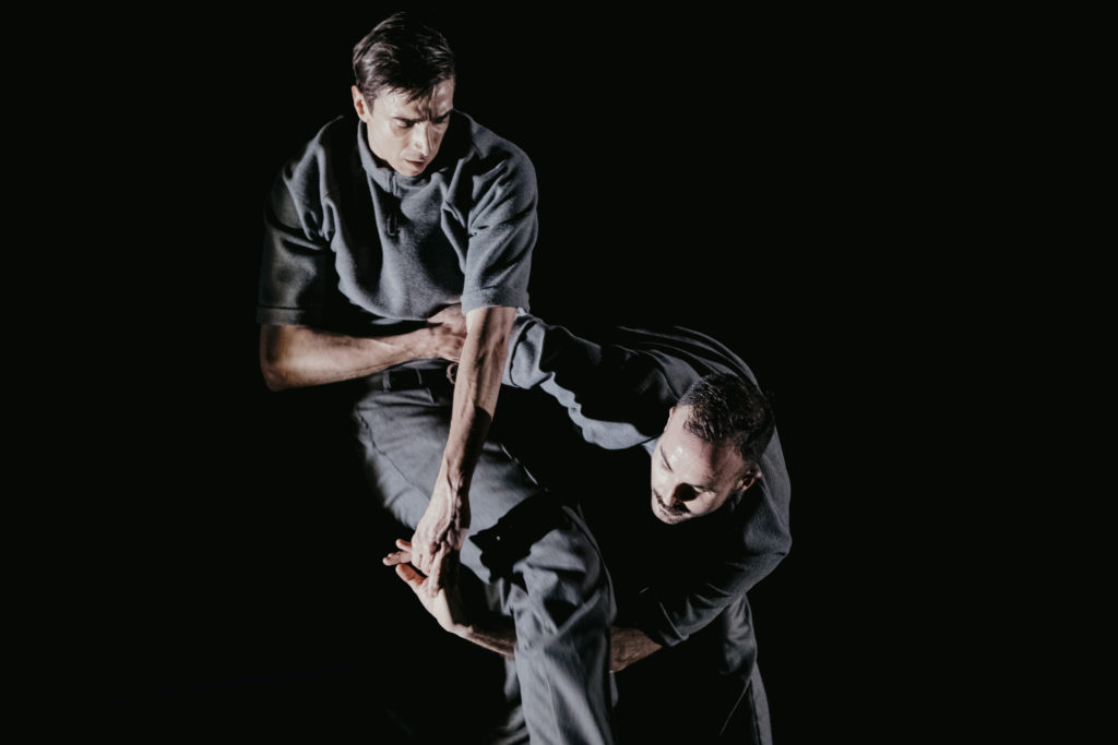 Two white male dancers in grey outfits link arms underneath one of the dancer's legs