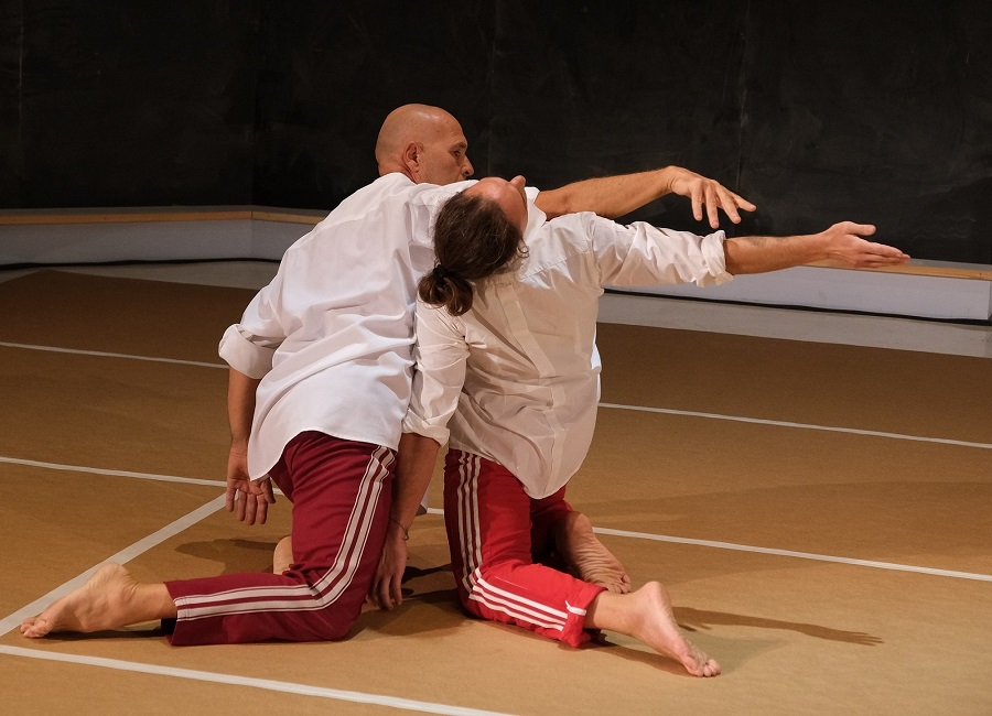 Two male dancers in tracksuits kneel while one brushes over the other