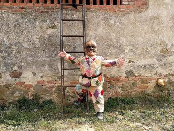 A man of short stature wearing a mask and colourful costume stands against a wall