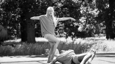 A disabled white female performer with blond hair balances on one leg above a man writhing on the floor. A black and white photo of a performance outside.