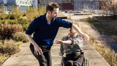 A female dancer with blonde hair using a wheelchair duets with a non-disabled male dancer outside in the sun.