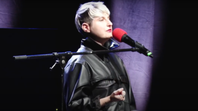 A performer with cropped bleached hair speaks passionately into a microphone