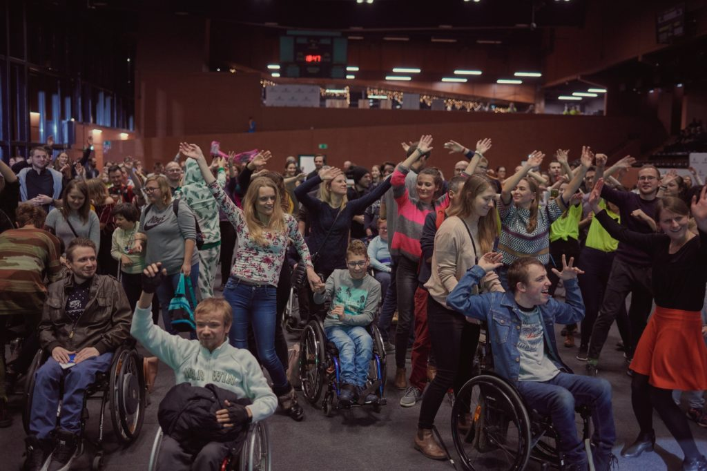 A group of people in a hall, cheering and waving hands above their heads. They participate in the music concert. Some of them are using wheelchairs.