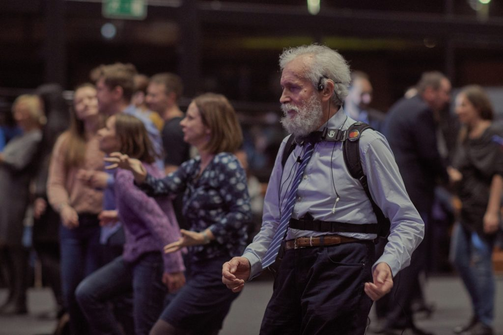 A man dancing and wearing a special set: a backpack and a headband vibrating to the beat of the music It is a set helping deaf people to feel music.