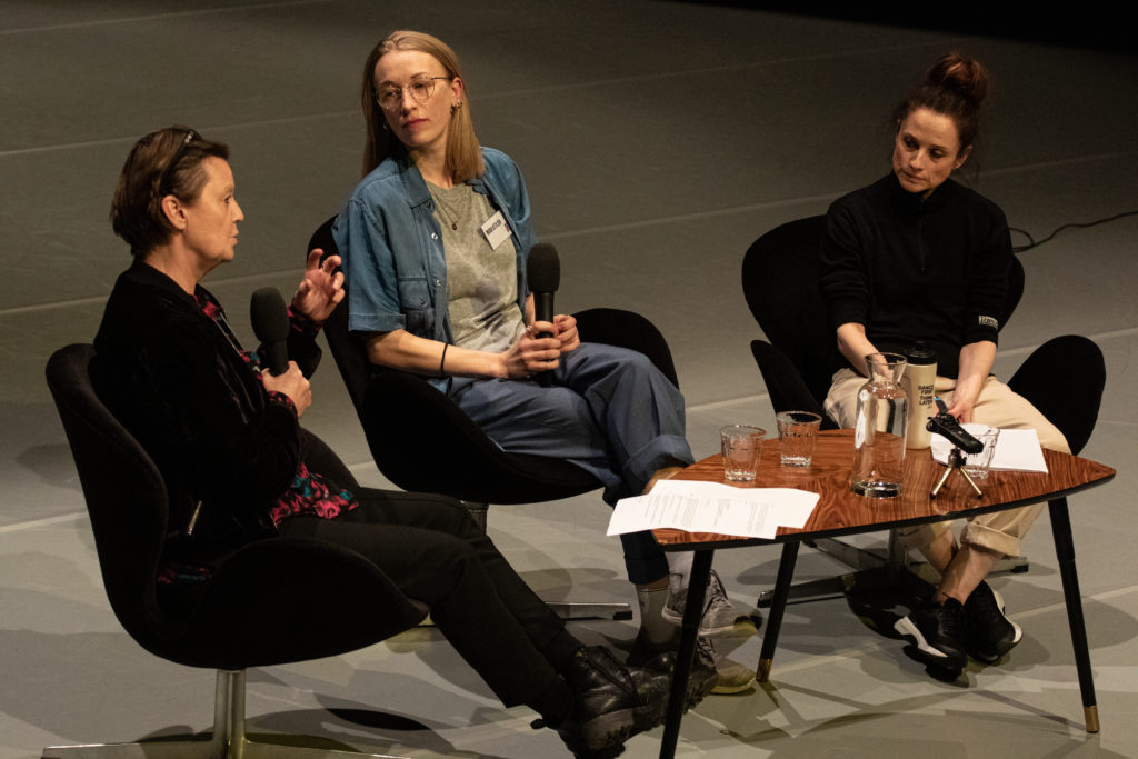 Three white women debating at a conference around a table