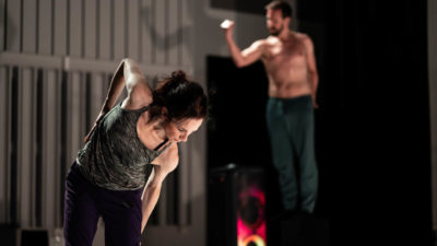 Female dancer leaning forwards, in the background a male dancer with his top off is clencing a fist